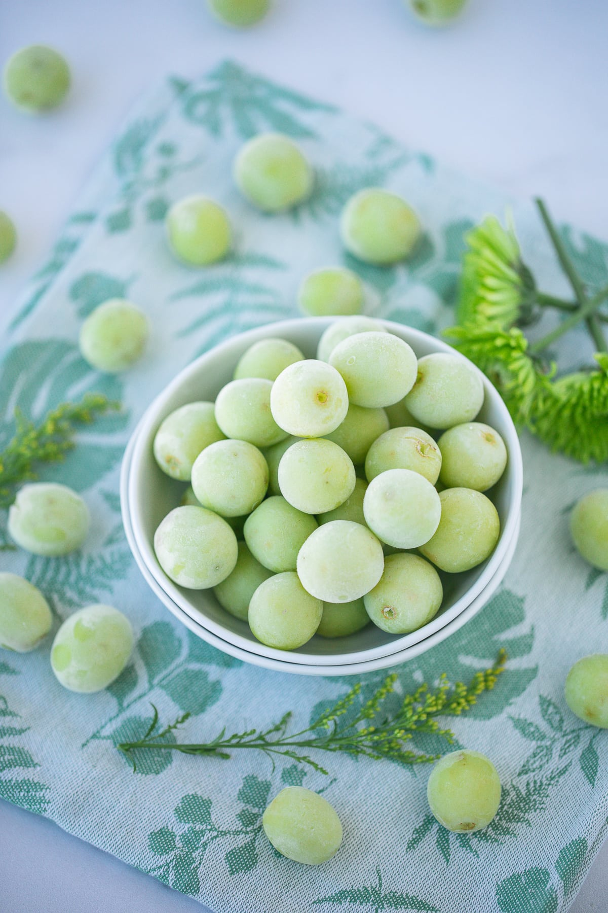 bowl of green frozen grapes on a countertop