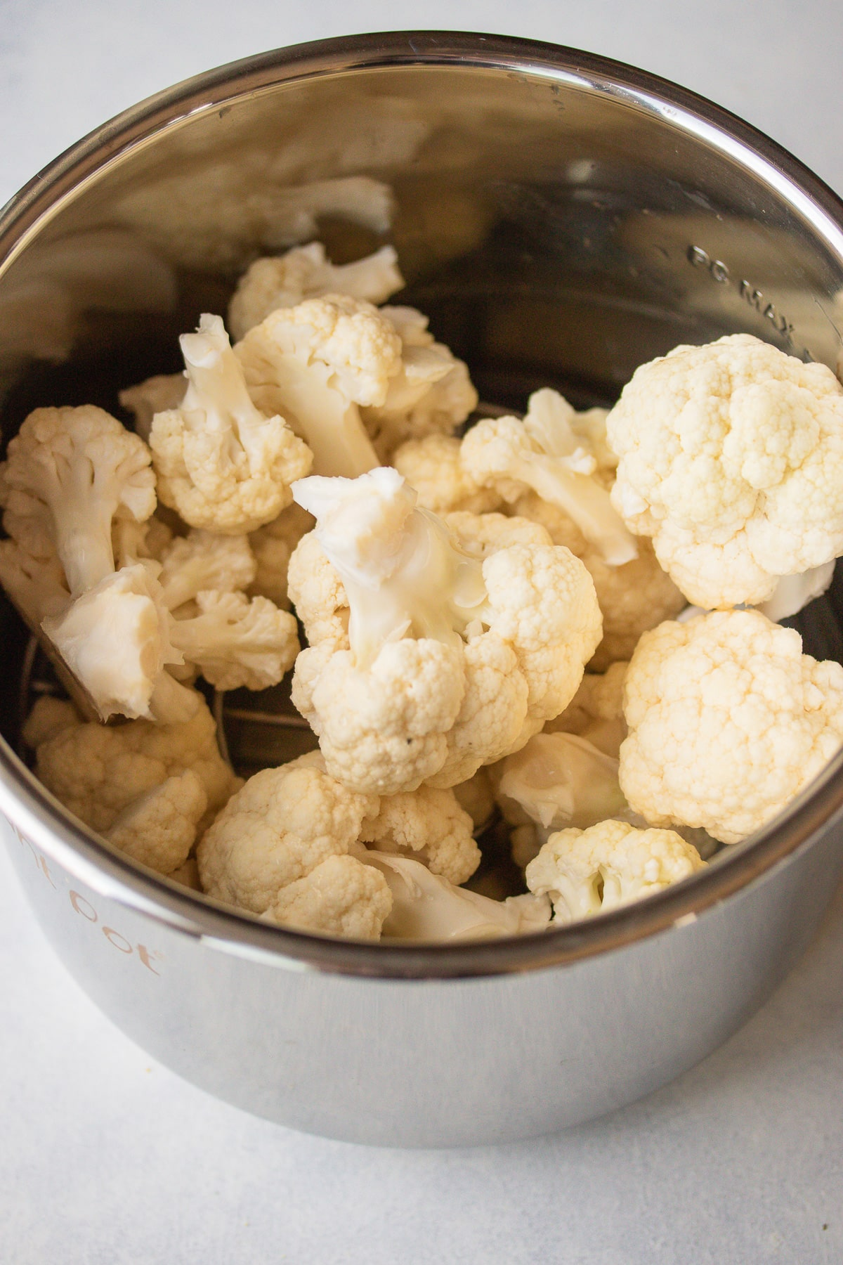 cauliflower florets in the base of a pressure cooker ready to be cooked