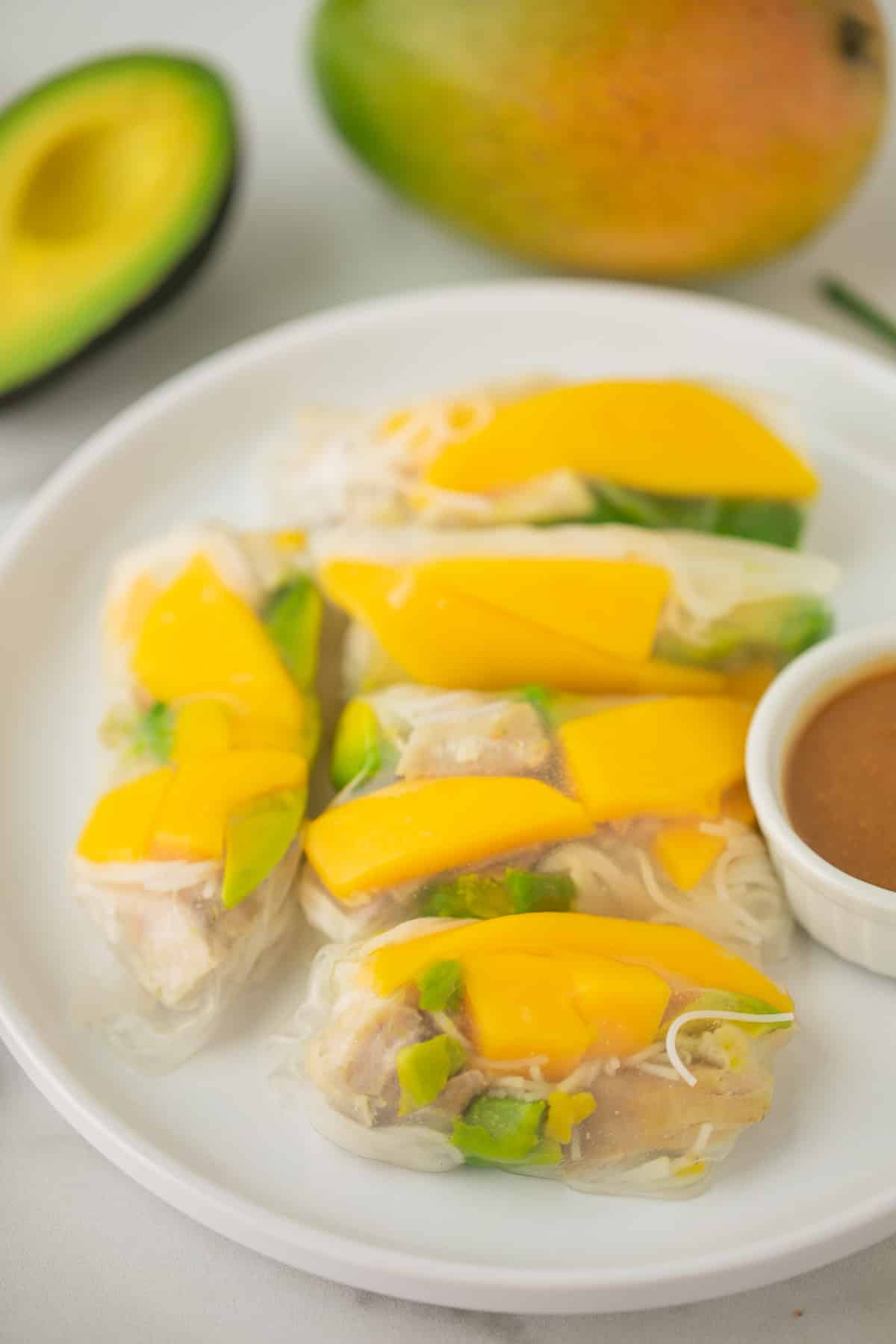 plate with mango summer rolls with a peanut dipping sauce