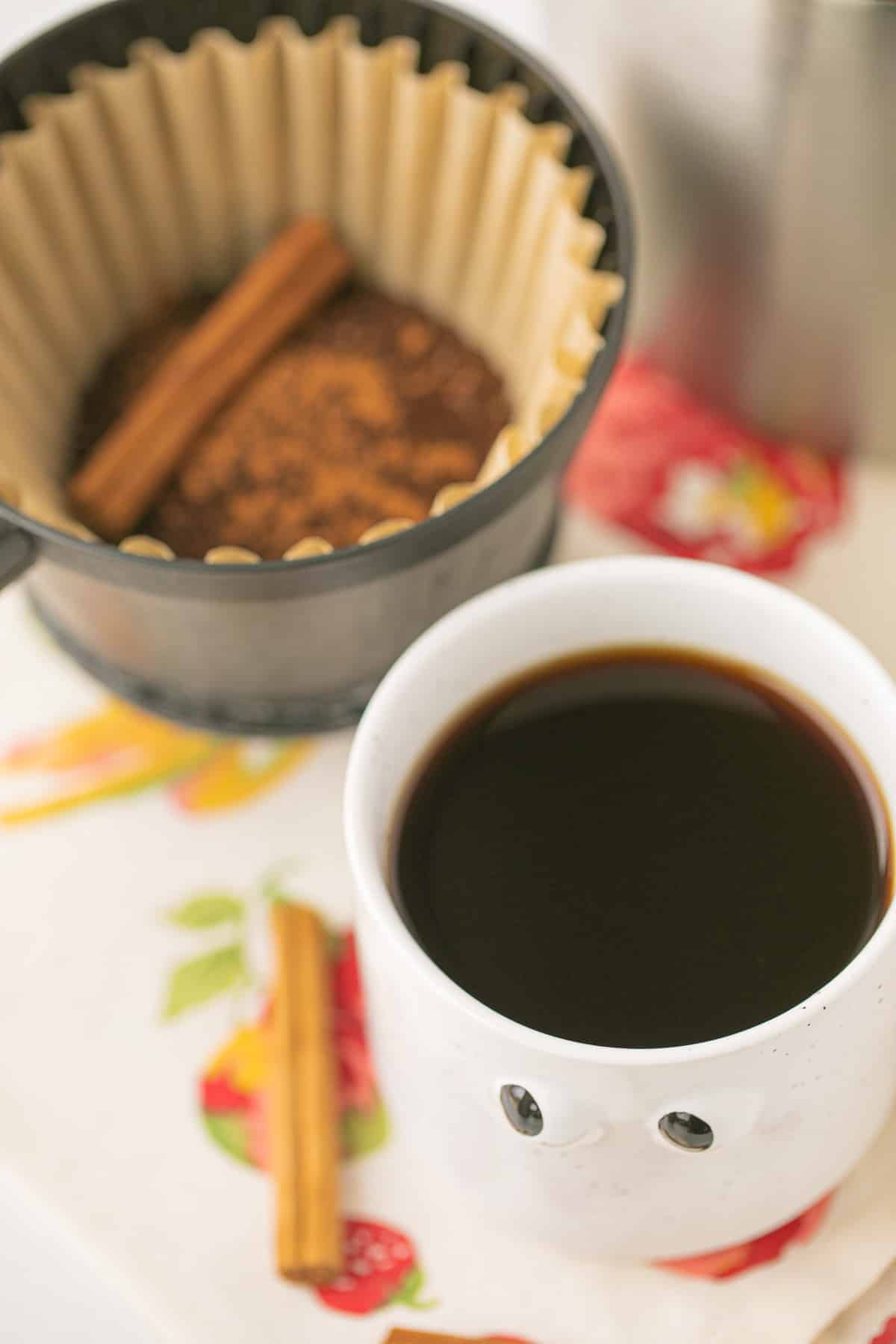 pumpkin spice coffee in a white mug next to cinnamon sticks