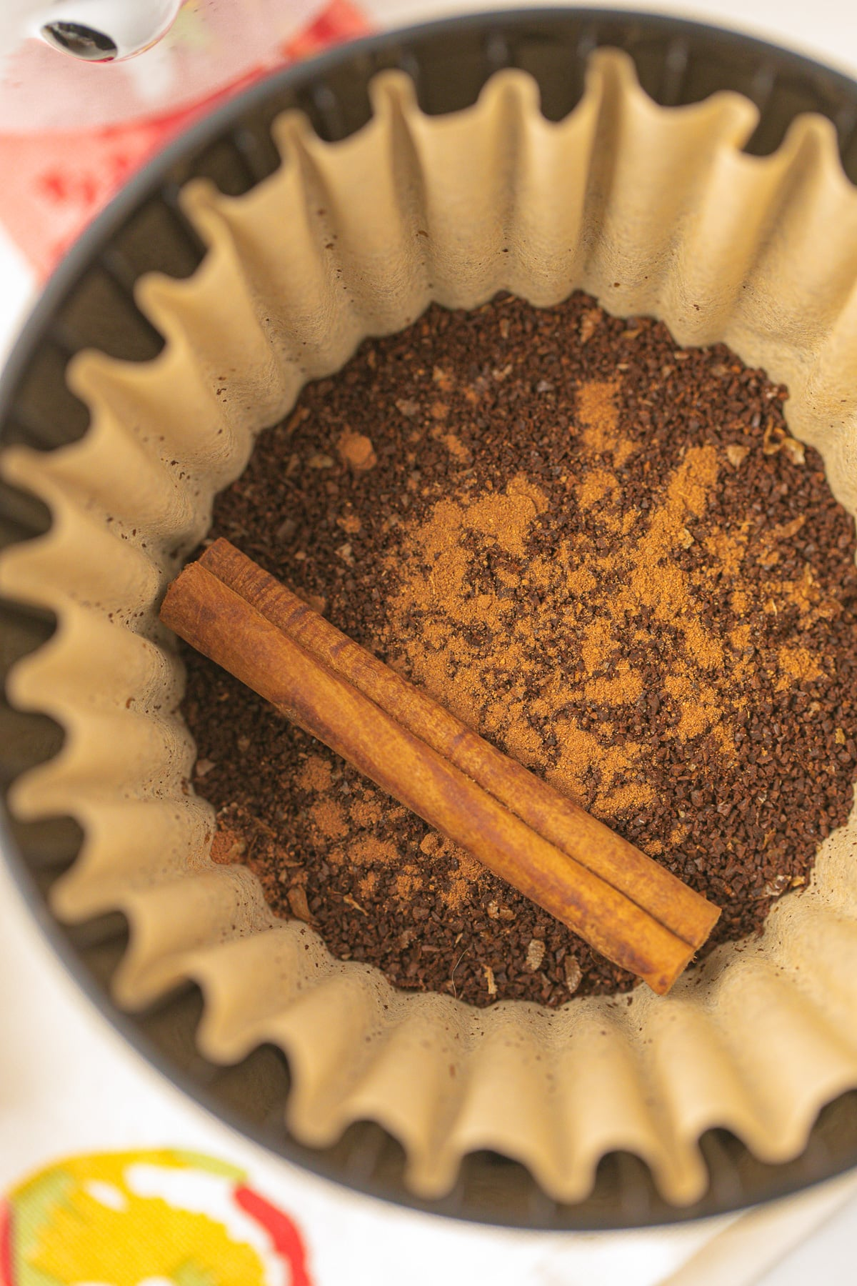 coffee filter with ground coffee, pumpkin spice, and a cinnamon stick