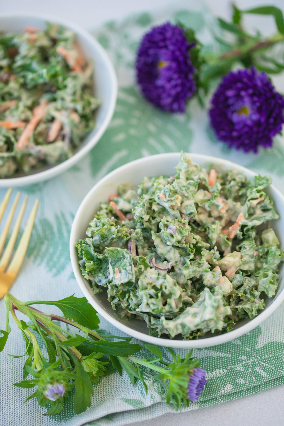 bowl of kale salad on a green floral napkin with fresh purple flowers