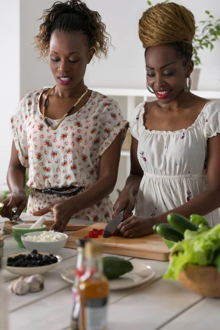 two women in a kitchen preparing food together
