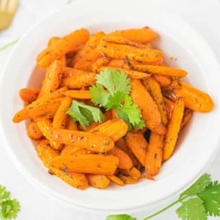 bowl of cooked carrots with two gold forks