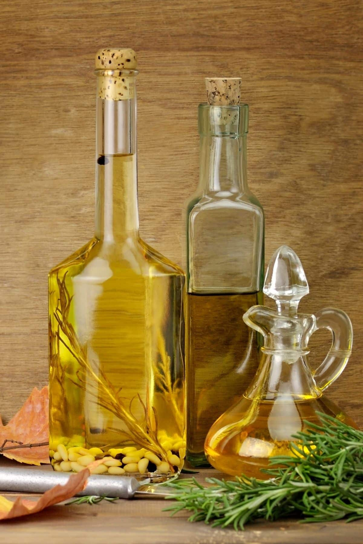 three jars of cooking oil in varying sizes and colors