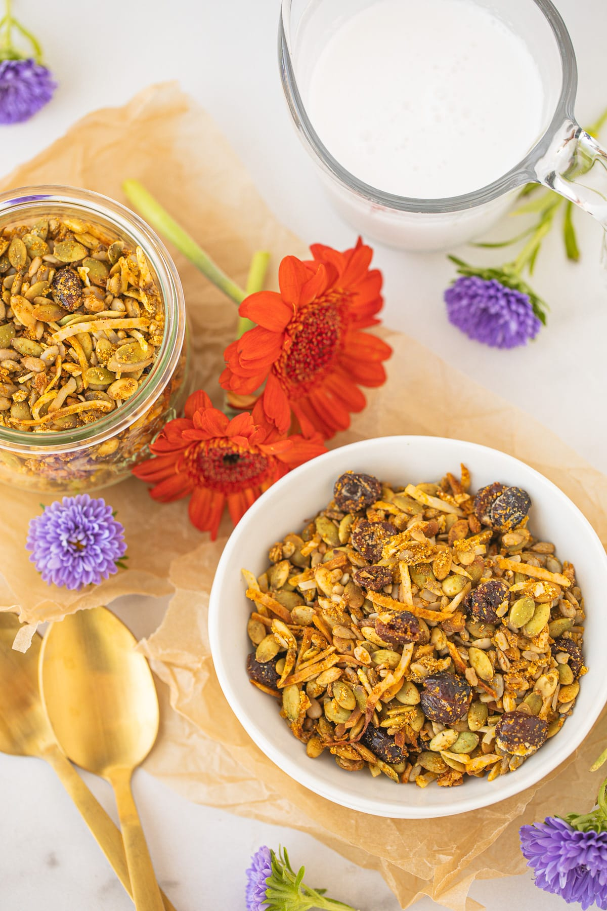 bowl of pumpkin granola with flowers and a gold spoon