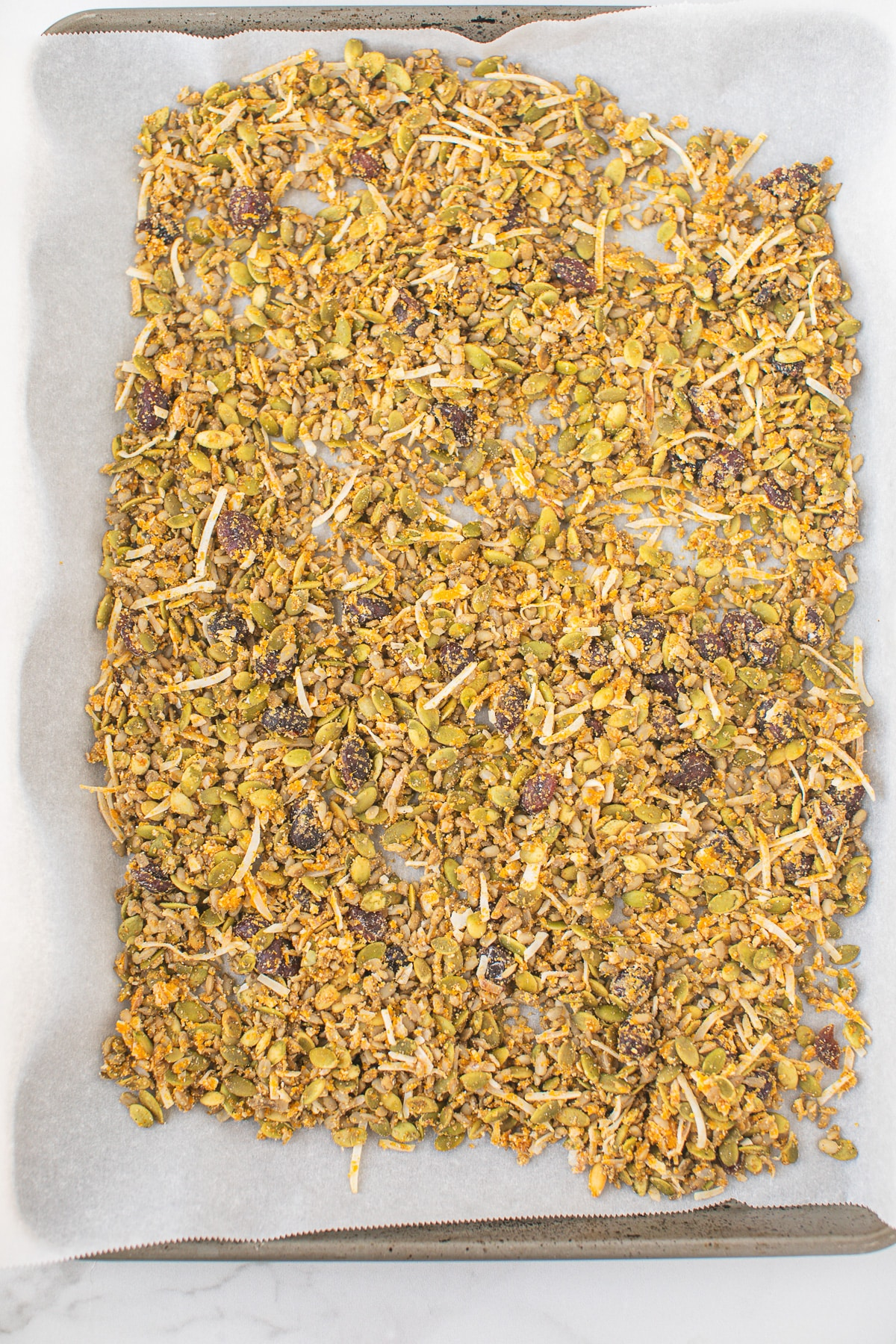 granola on a baking sheet ready to be cooked