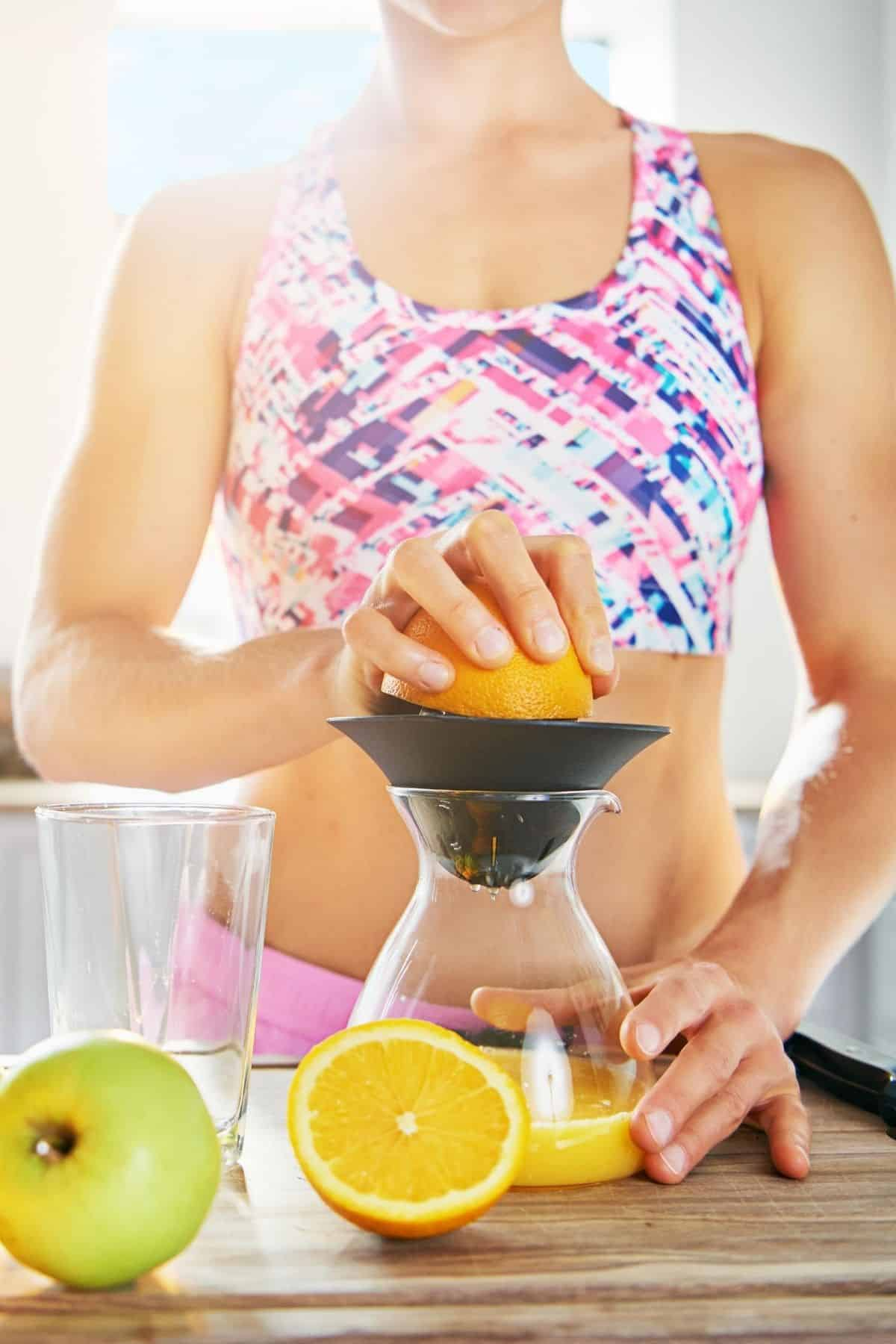 woman in a bright kitchen making juice