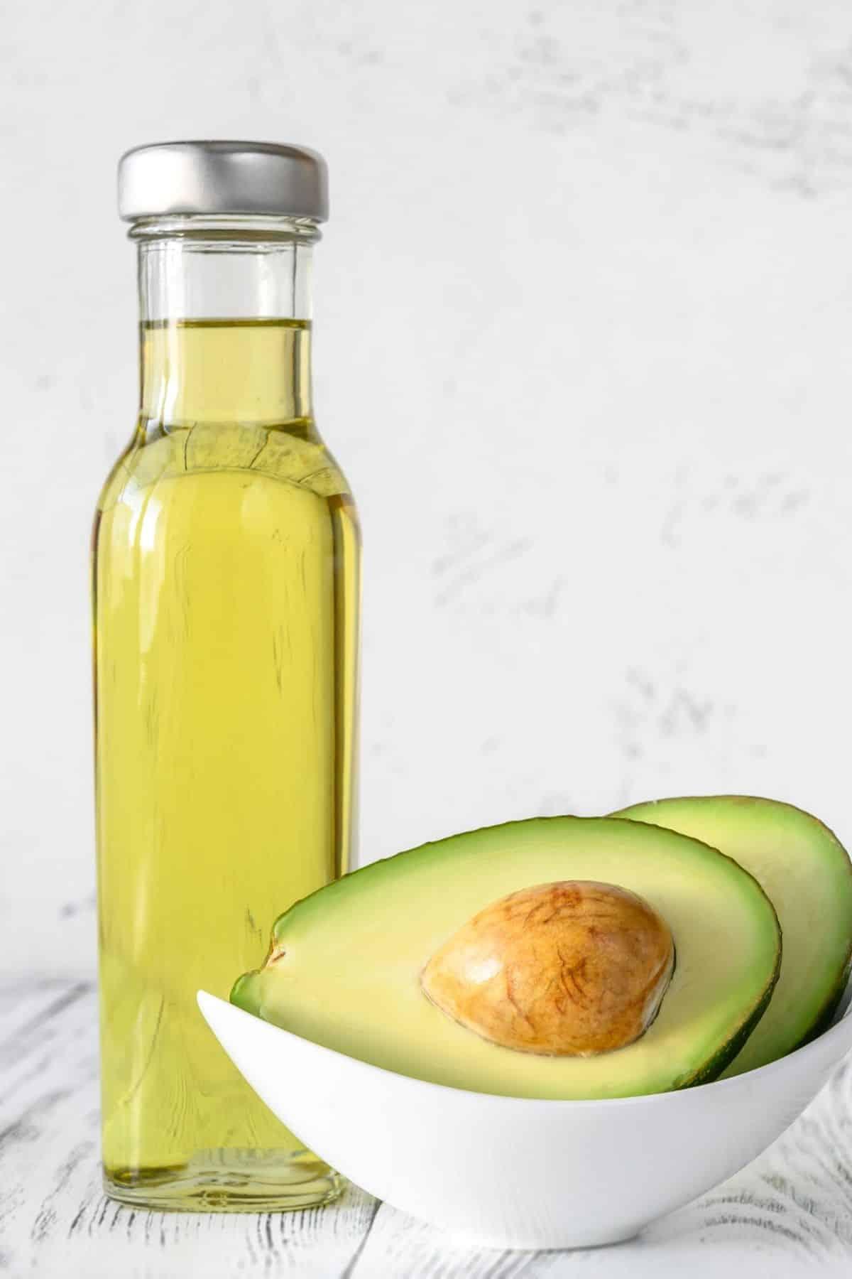 jar of avocado oil with a sliced fresh avocado next to it