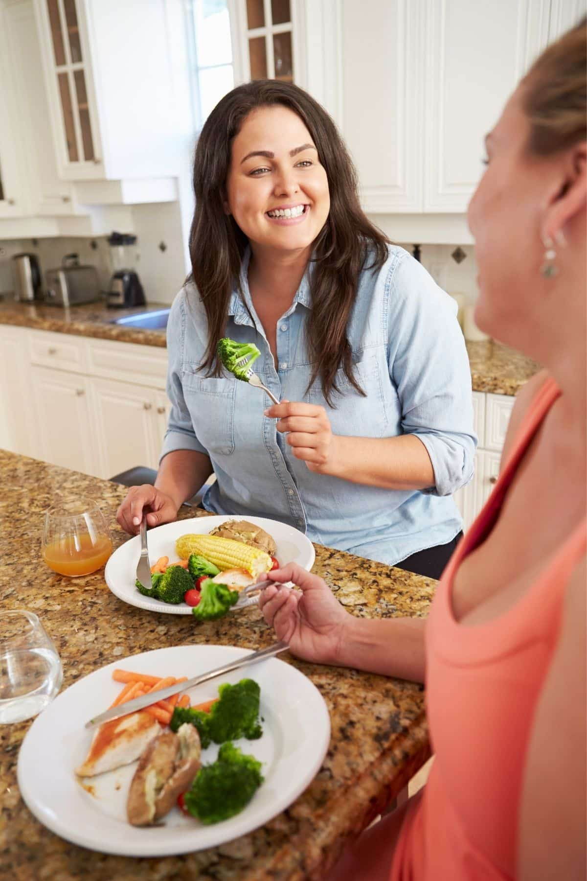 two women eating together in a kitchen