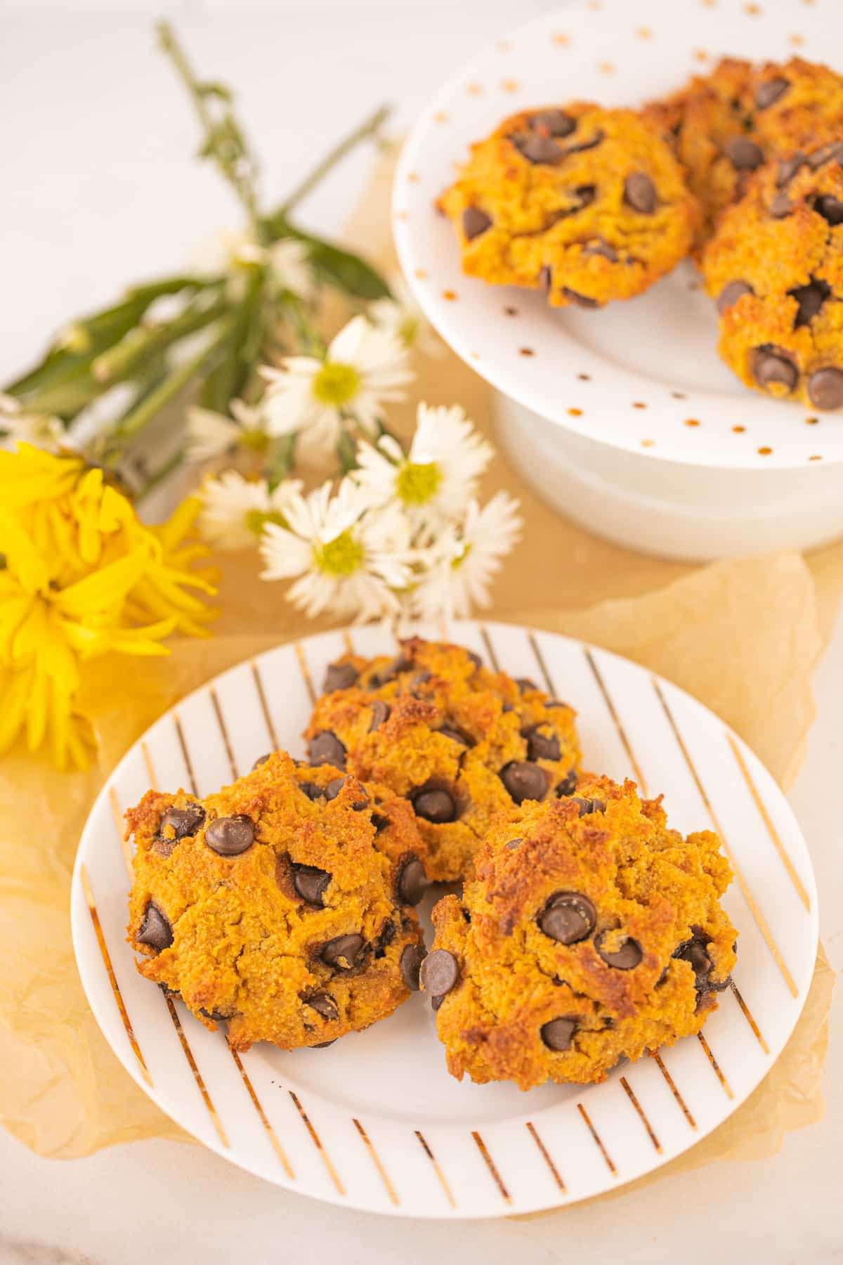 two plates of vegan pumpkin chocolate chip cookies with fresh flowers