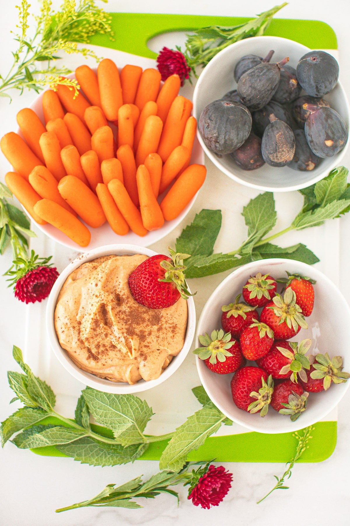 dip served with baby carrots, strawberries, and figs