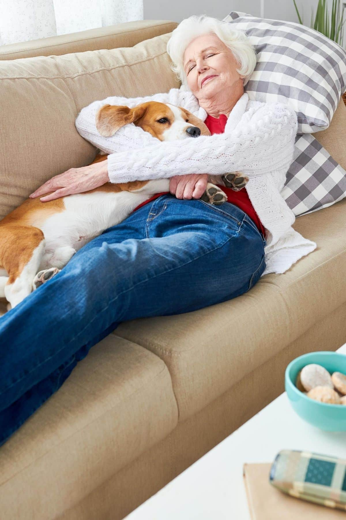 woman on couch napping with her dog
