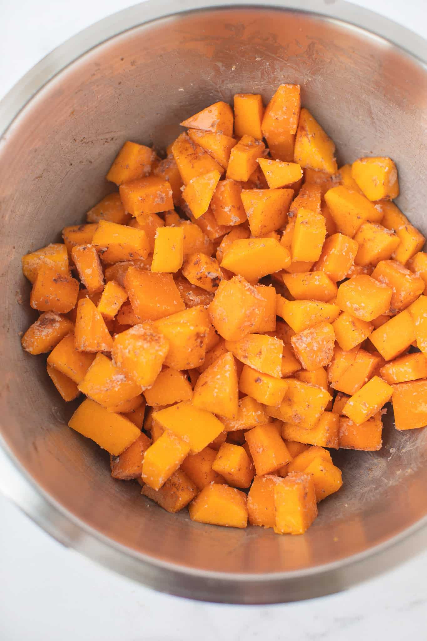 bowl of cubed butternut squash with coconut oil ready to be baked
