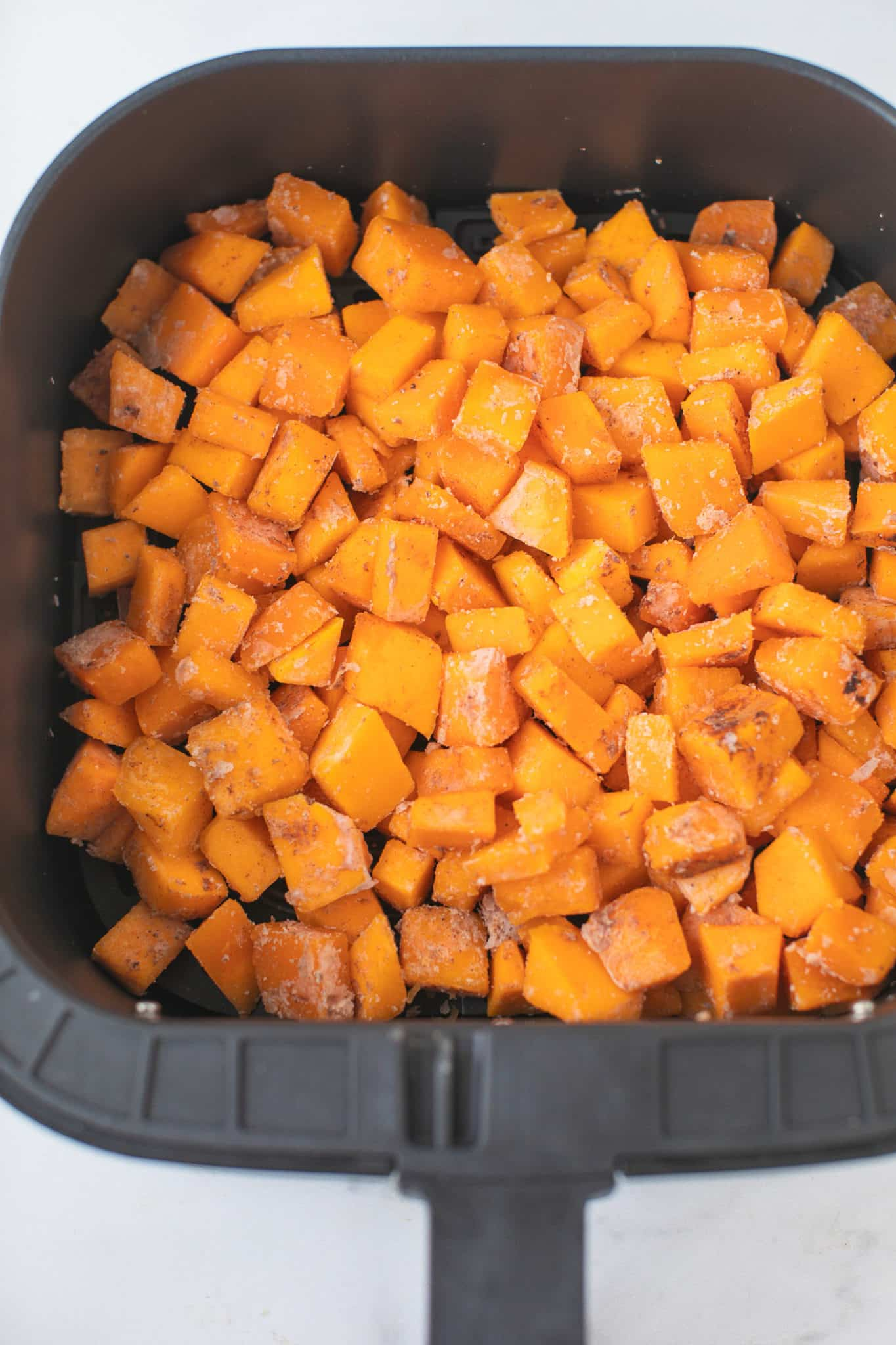 squash cubes in an air fryer basket ready to be cooked