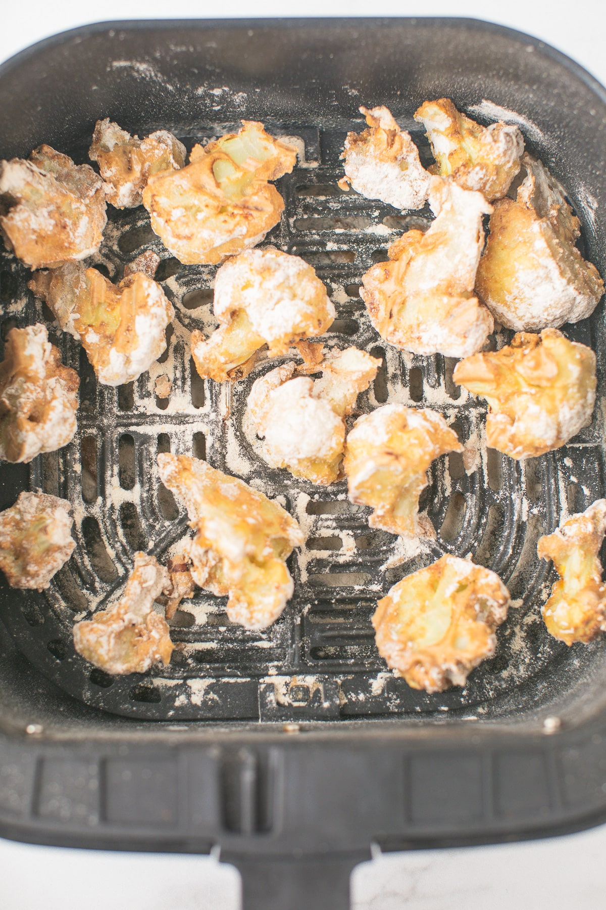 cooked cauliflower in the air fryer basket