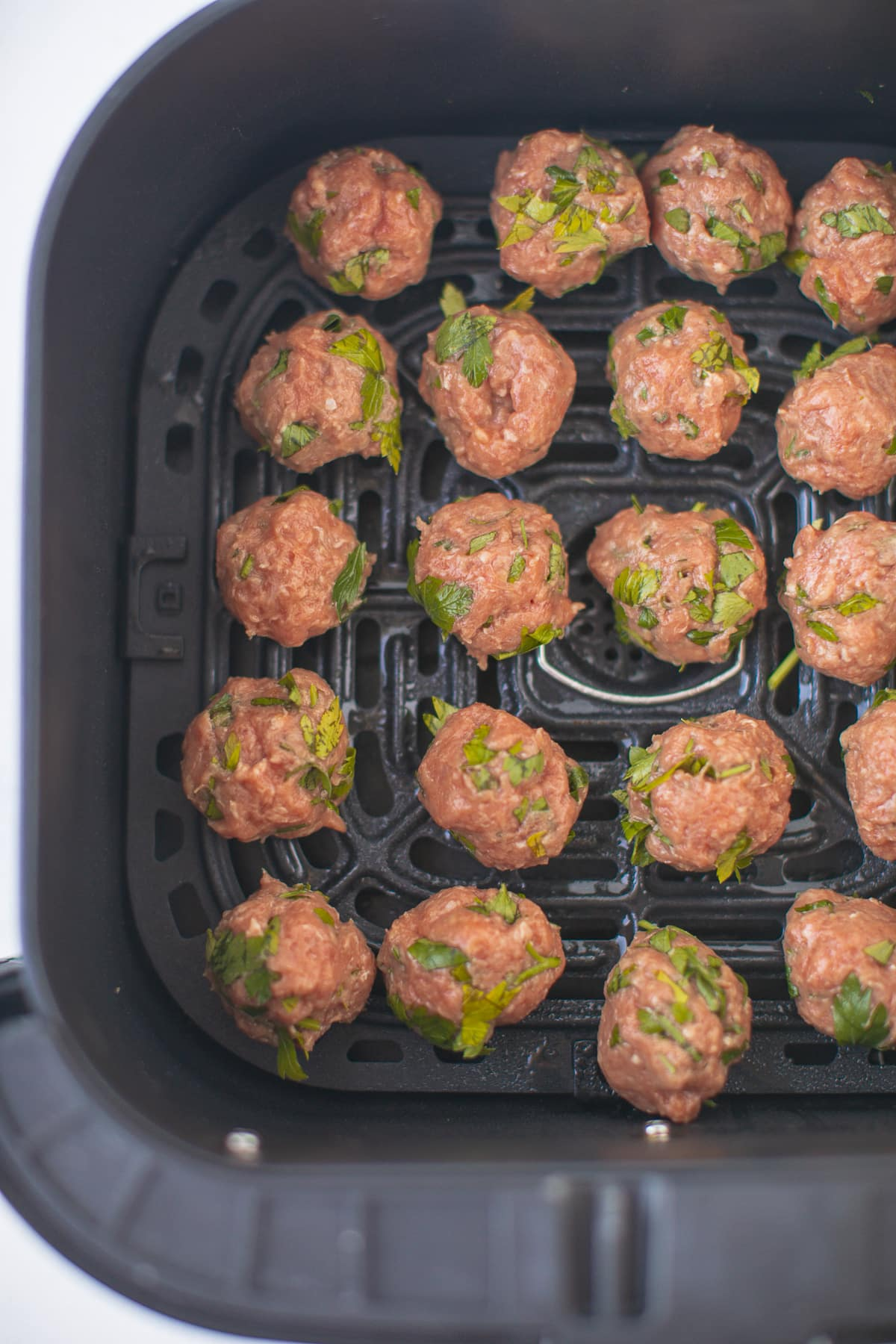 uncooked meatballs in the basket of an air fryer