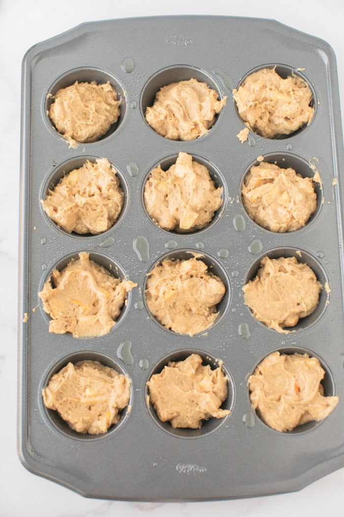 apple muffin batter in a muffin tray