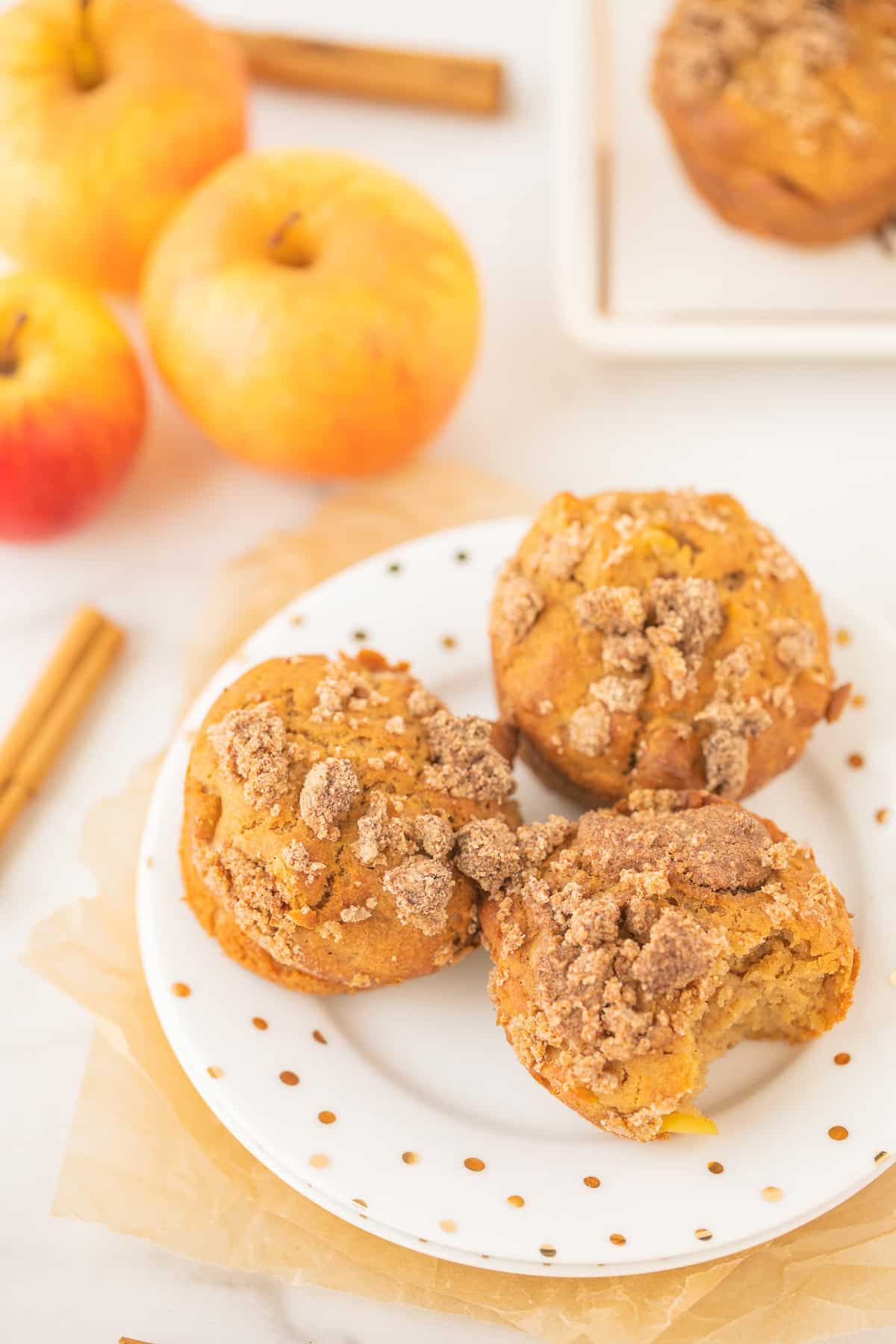 apple muffins on a plate with fresh apples and cinnamon sticks on a countertop