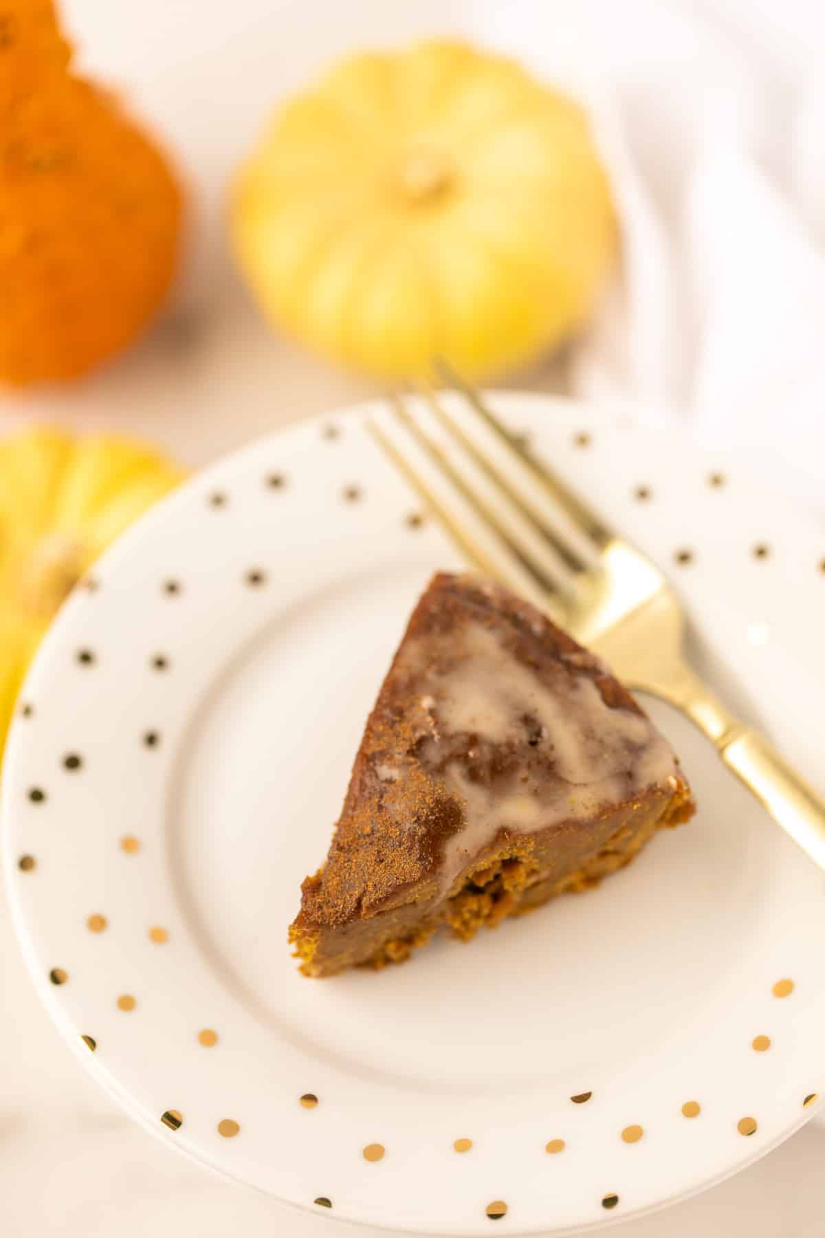 slice of baked instant pot pumpkin cake with drizzle on top and a gold fork