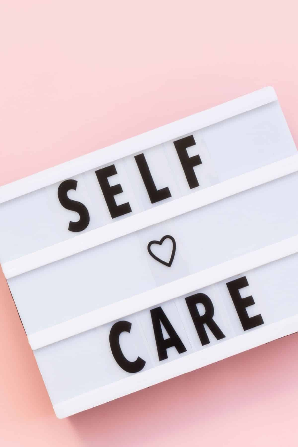 sign with self care in black letters