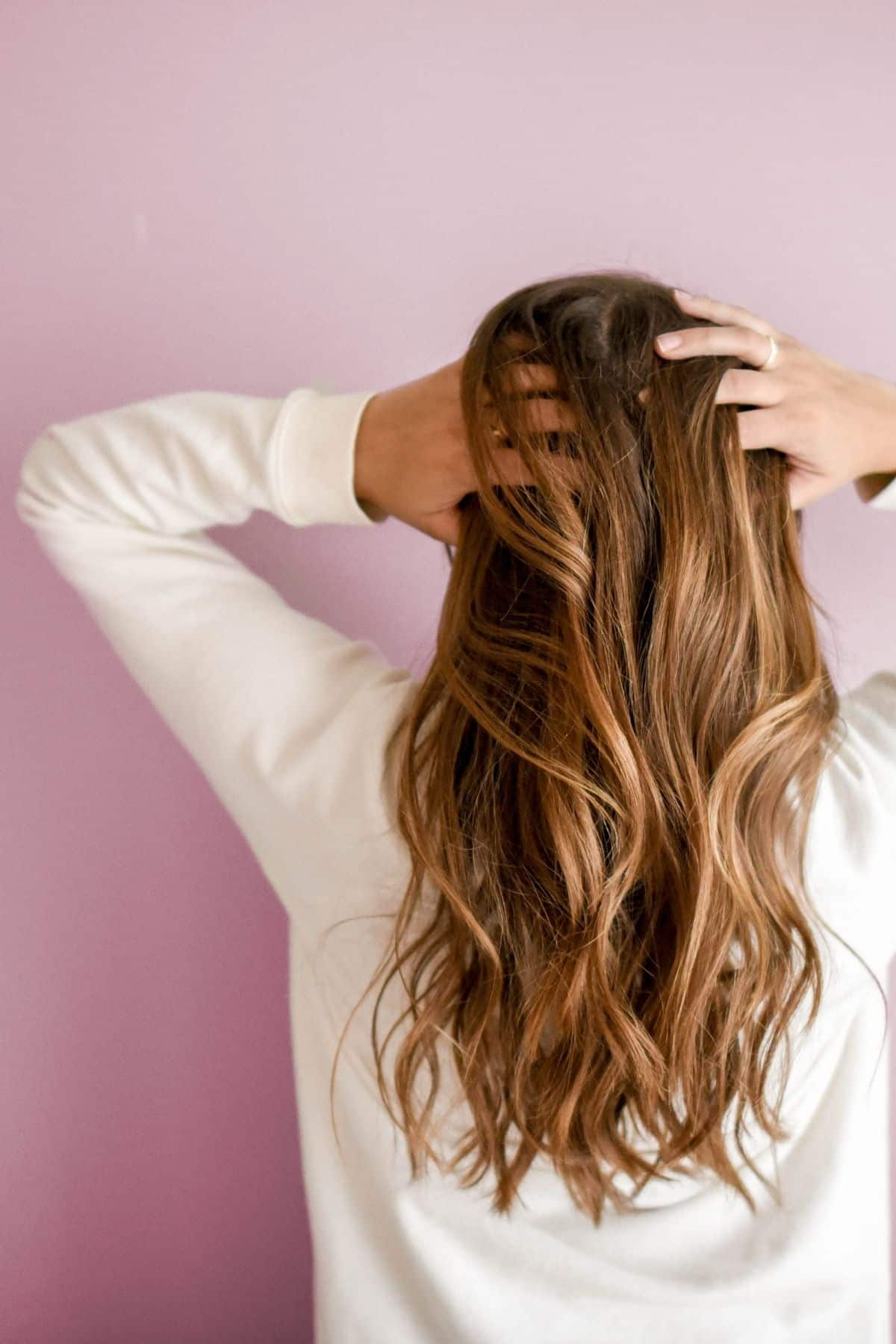 woman with long brown hair holding her head