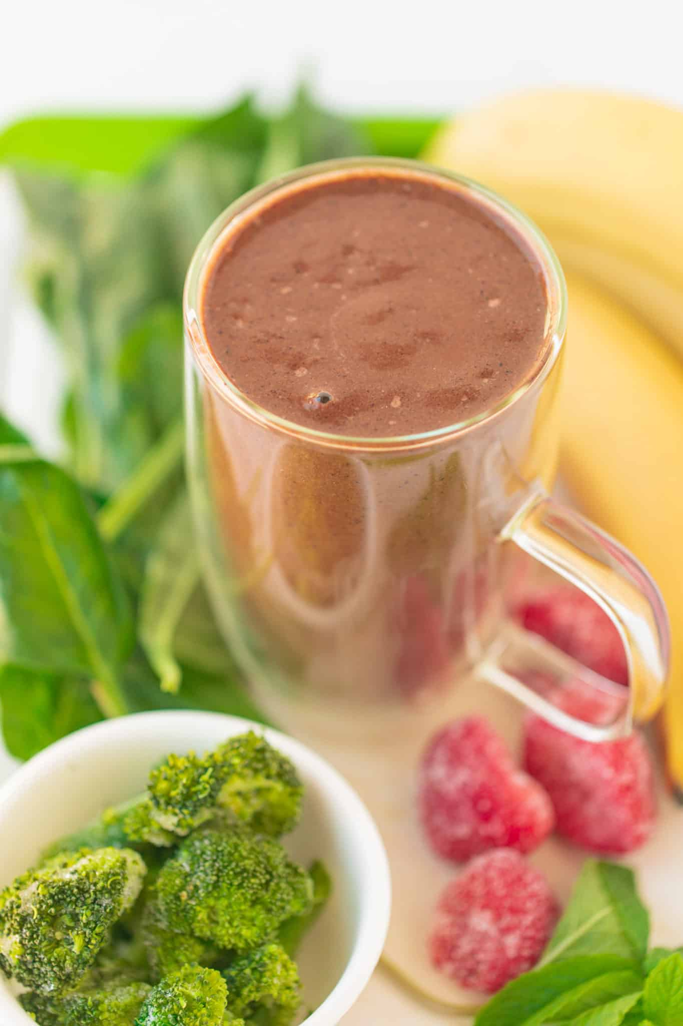 dark pink smoothie served in a glass surrounded by broccoli, greens, bananas, and strawberries