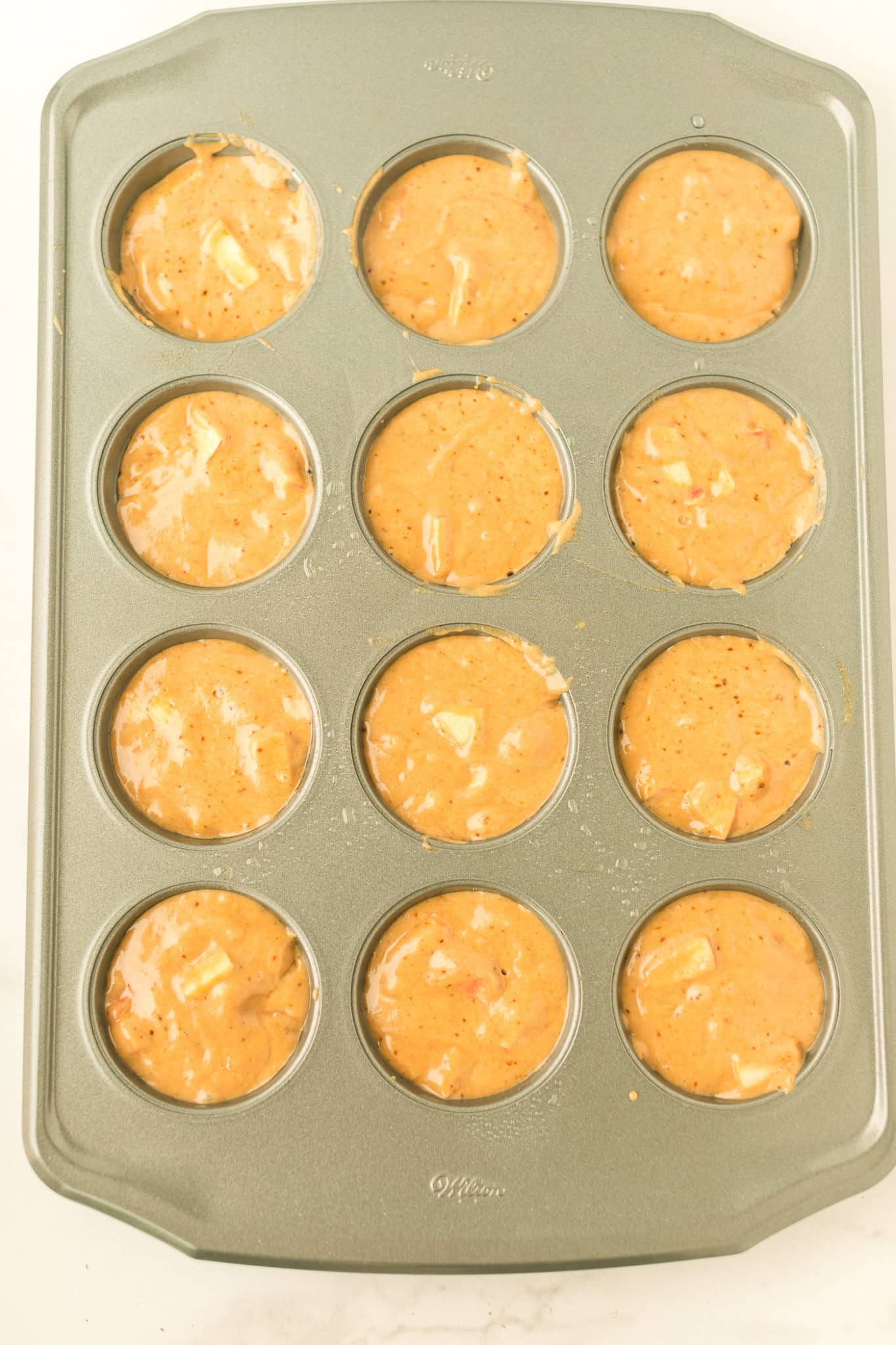 apple cider muffin batter in a muffin tray ready to be baked