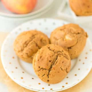 plate with three baked apple cider muffins on it