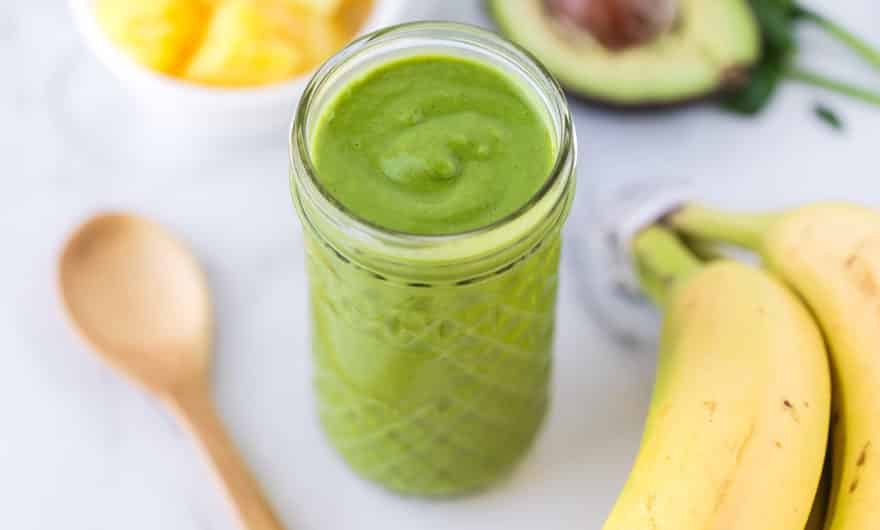 detox smoothie in a glass surrounded by a spoon, bananas, avocado, and pineapple