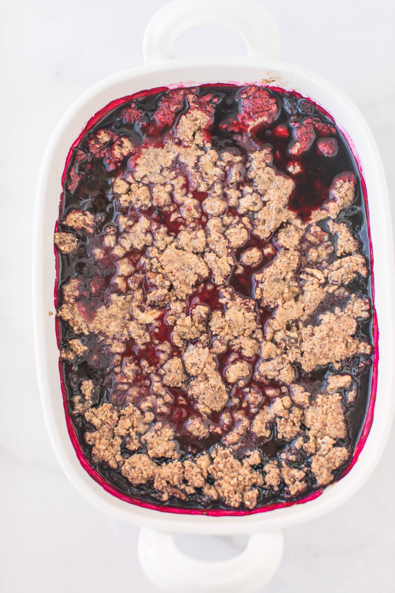 baked berry crisp in a white serving dish