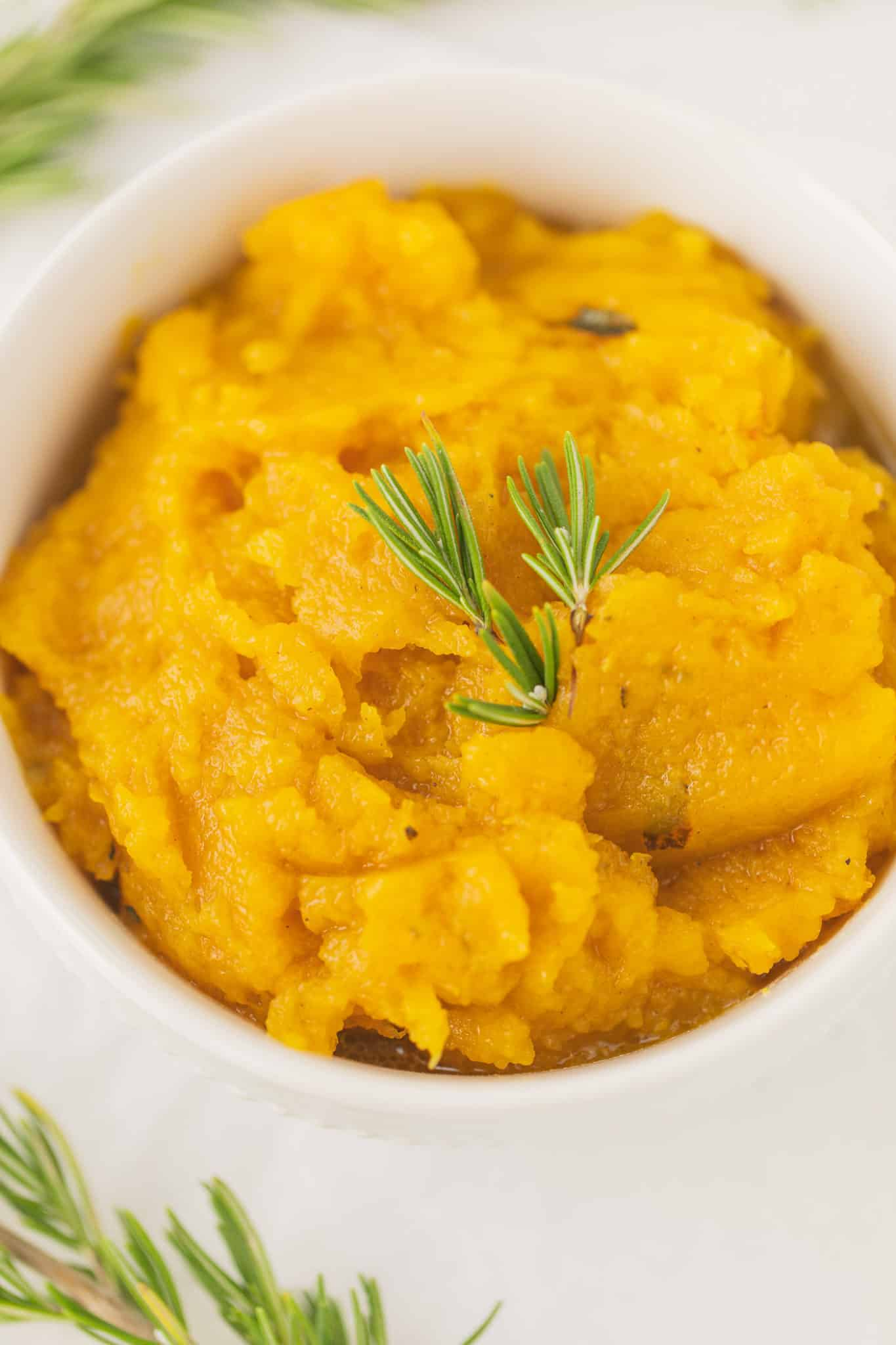cooked acorn squash puree served in a white bowl with a sprig of fresh rosemary