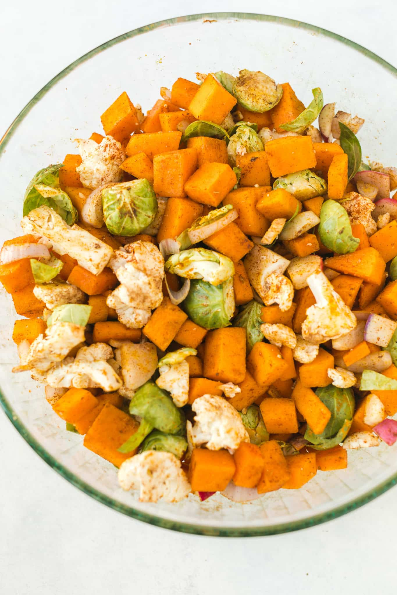chopped vegetables in a large mixing bowl tossed with oil and spice blend