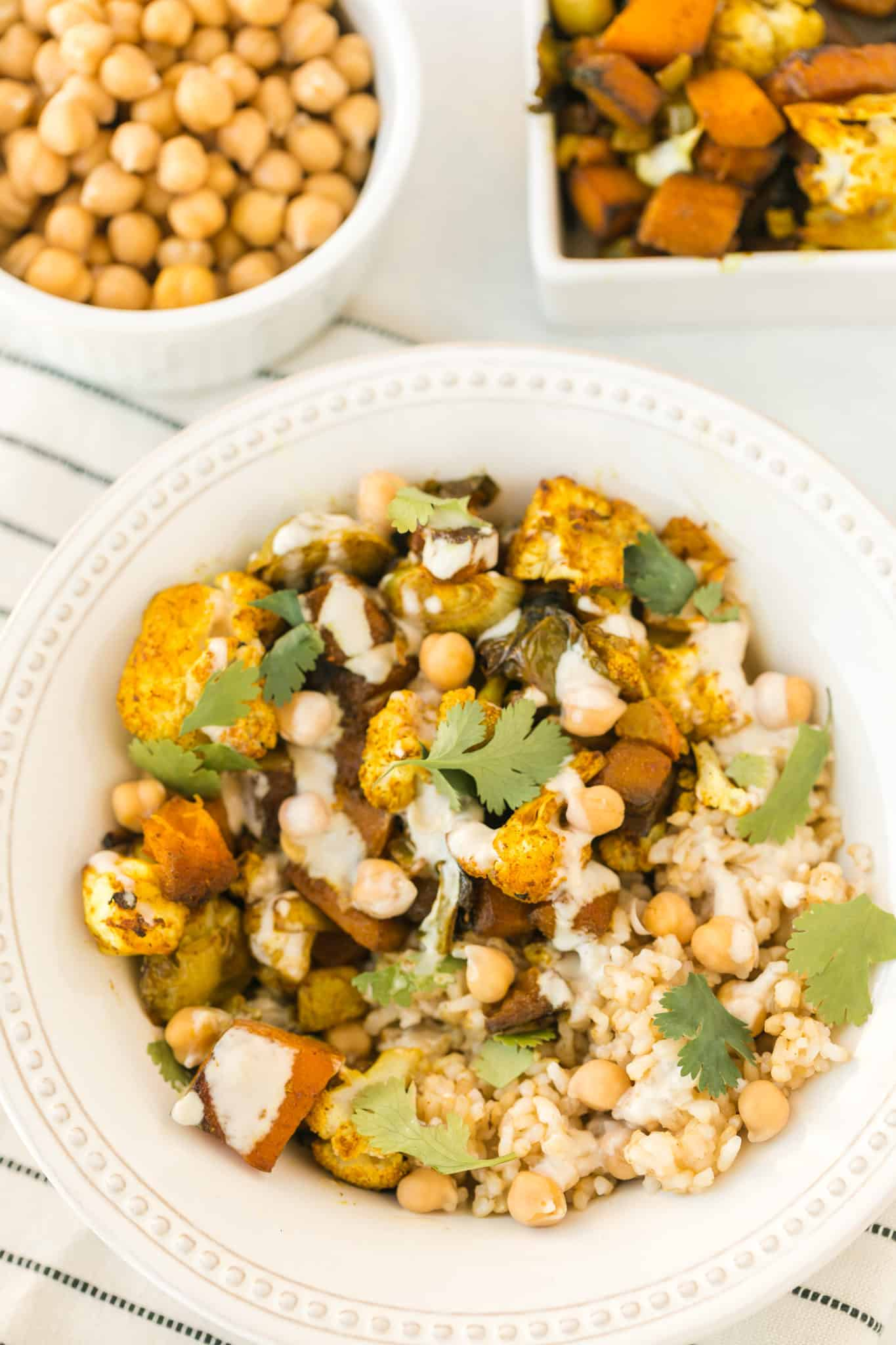 anti-inflammatory veggie bowl served with chickpeas and a tahini drizzle