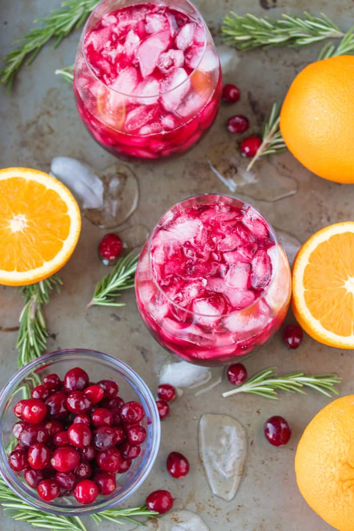 pomegranate cranberry mocktail served with crushed ice on a tray with fresh rosemary sprigs