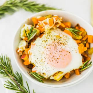 sweet potato hash served in a white bowl with a fried egg on top