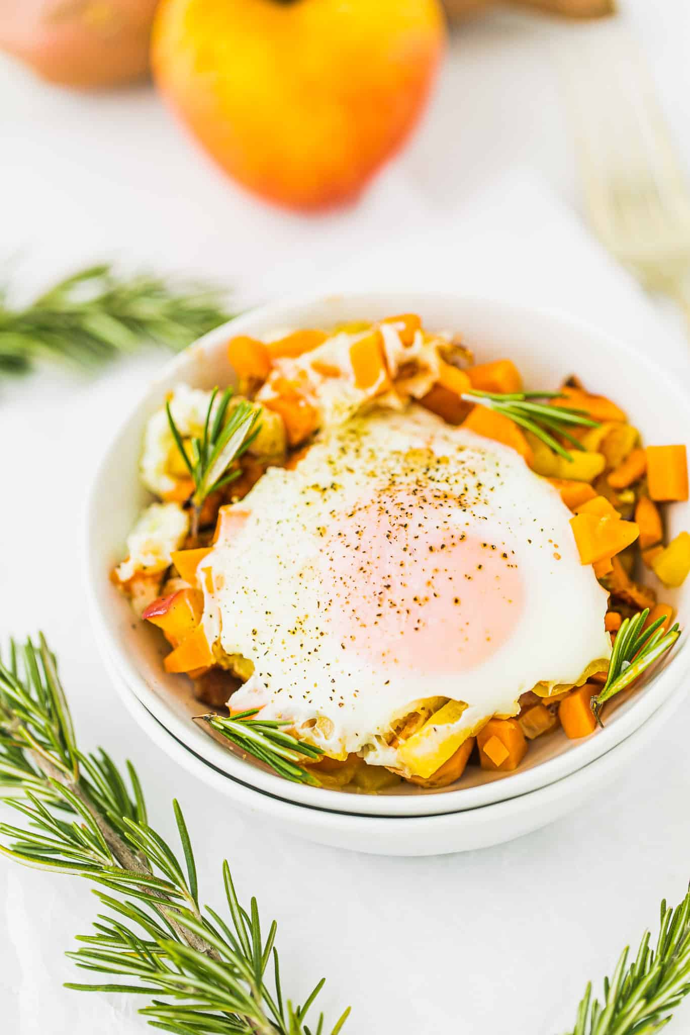 sweet potato apple hash with an egg served on a table with fresh sprigs of rosemary