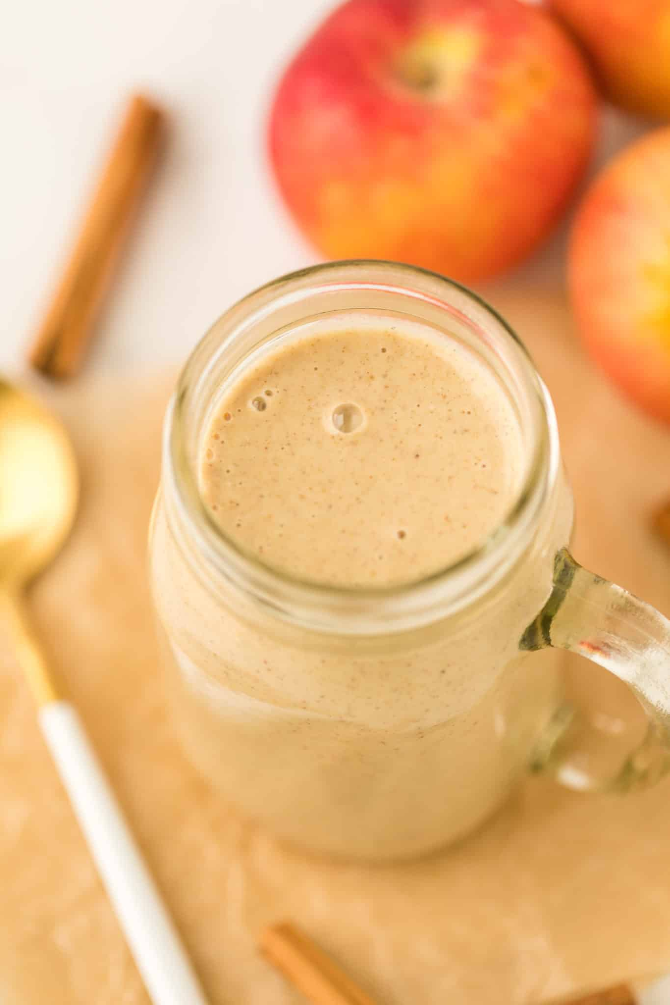 apple pie smoothie served in a glass jar on a table with fresh apples and cinnamon sticks