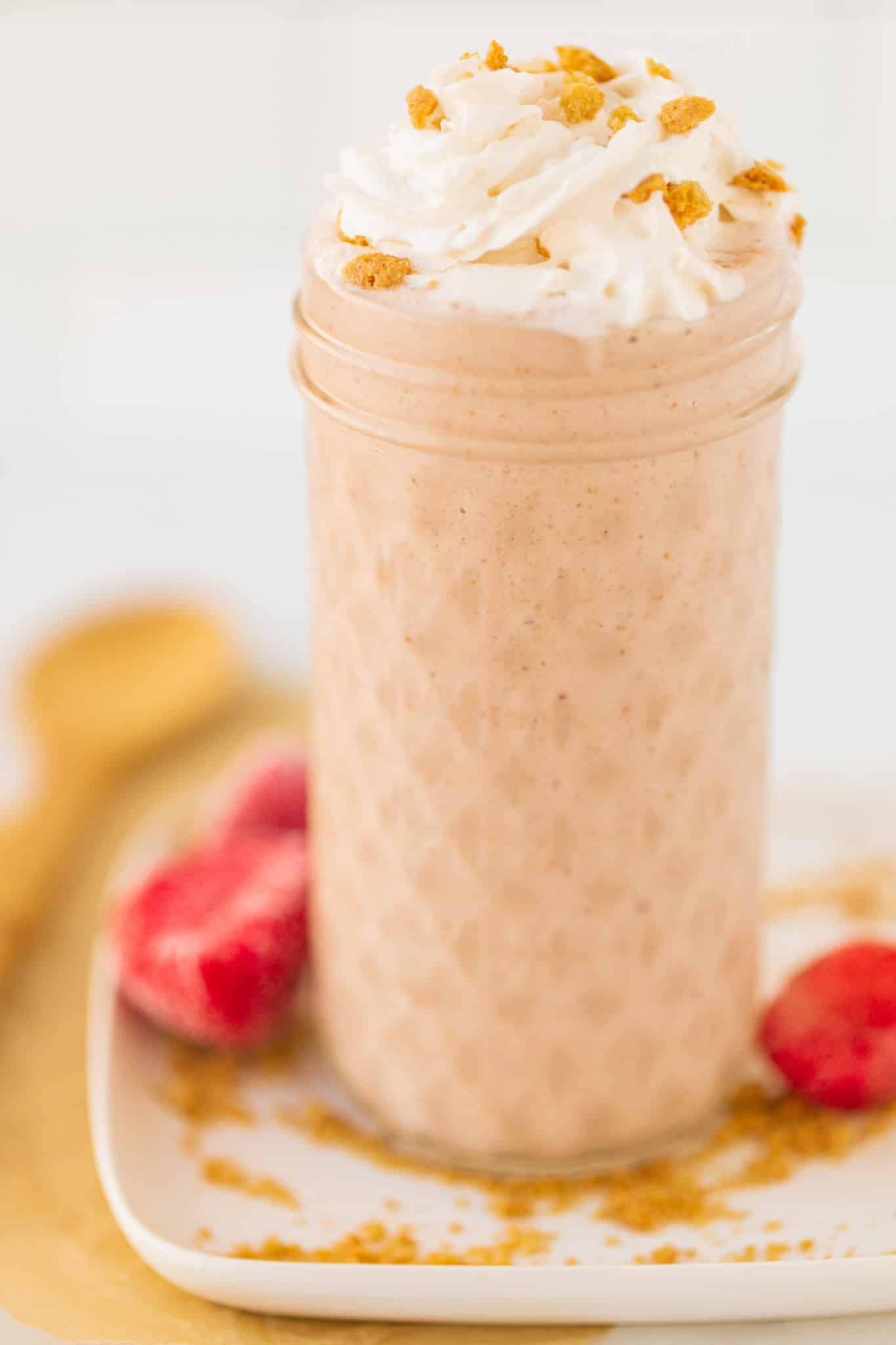 strawberry cheesecake smoothie served with whipped cream and crumbled vanilla wafer cookies