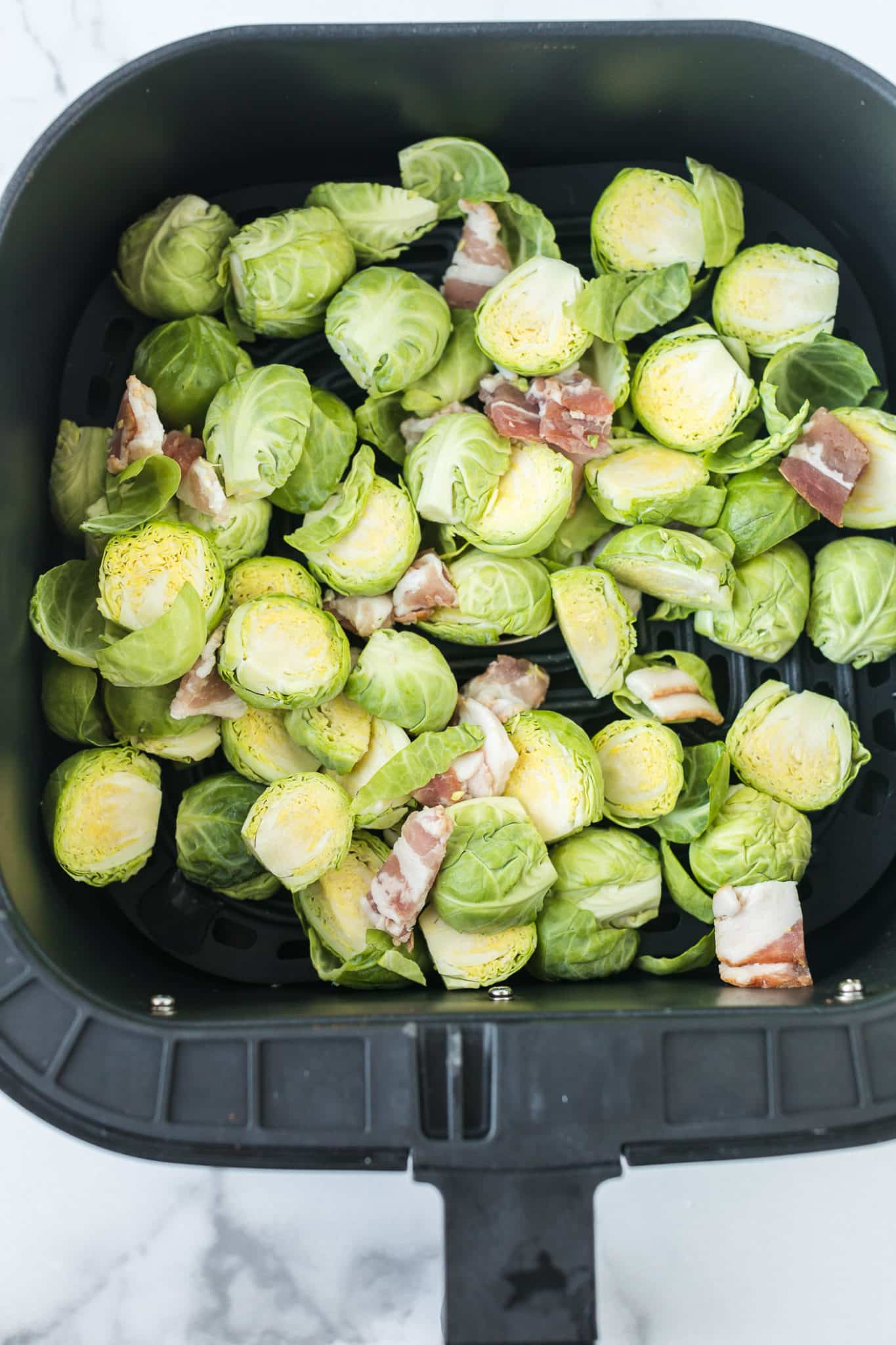 bacon and brussels sprouts in the basket of an air fryer ready to be cooked