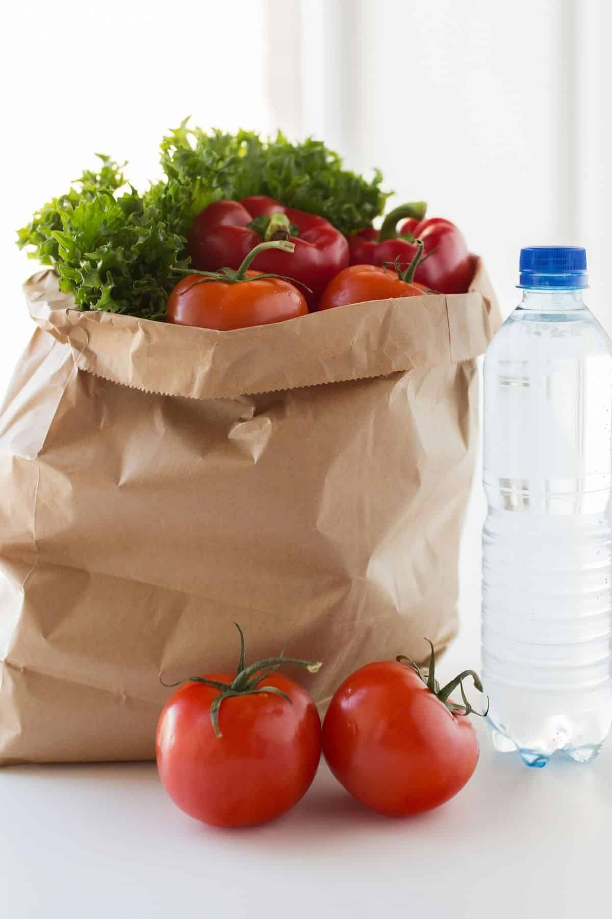 vegetables in grocery bag on a countertop with a bottle of water