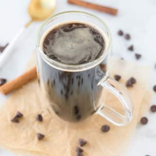 healthy hot chocolate on a table with chocolate chips and cinnamon sticks