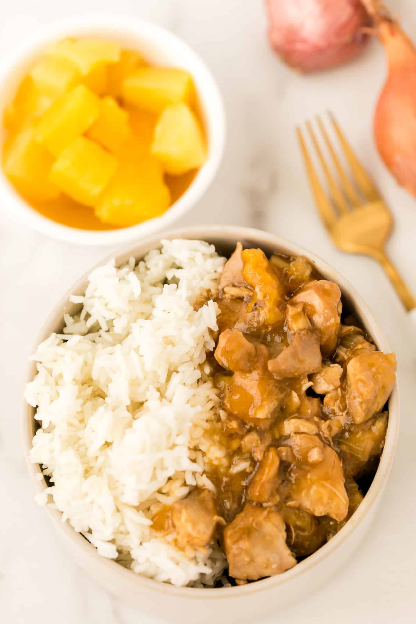 bowl of instant pot pineapple chicken served with white rice and a bowl of pineapple chunks