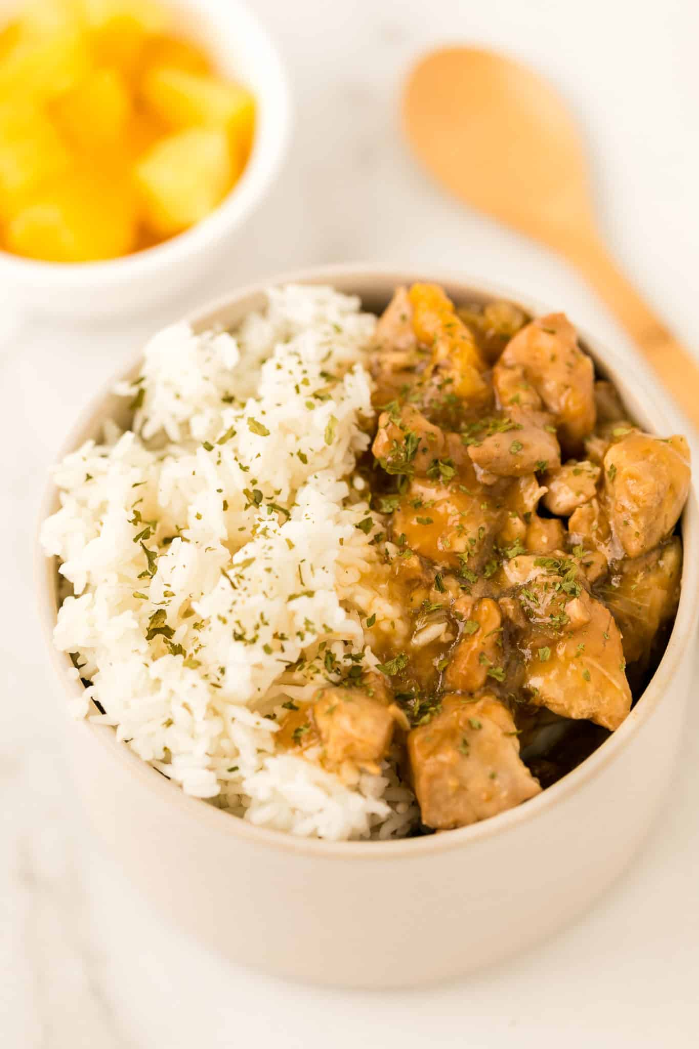 instant pot teriyaki chicken served in a bowl with white rice and sprinkled with parsley