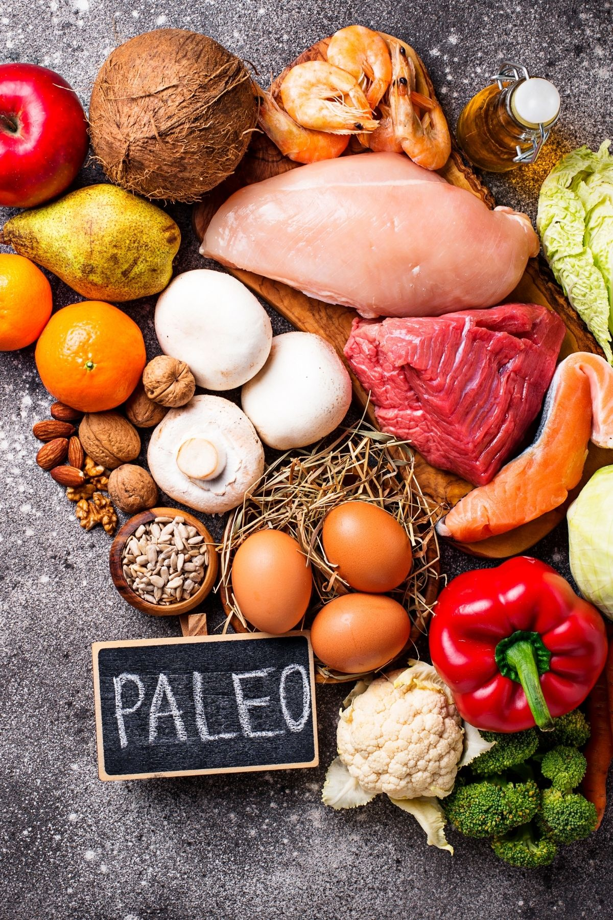 paleo diet foods on a table including meats, vegetables, fish, and eggs
