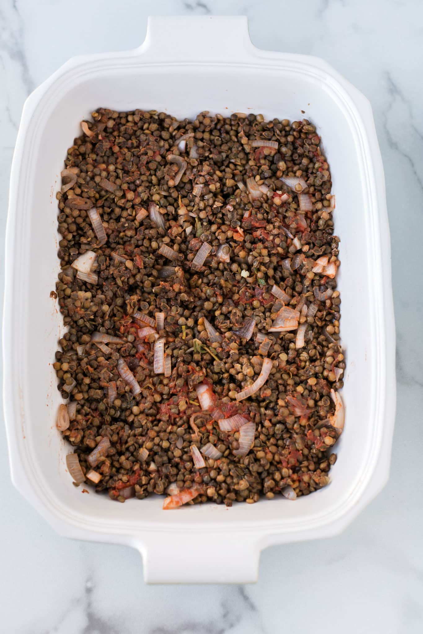 cooked lentils and onions in the bottom of a baking dish