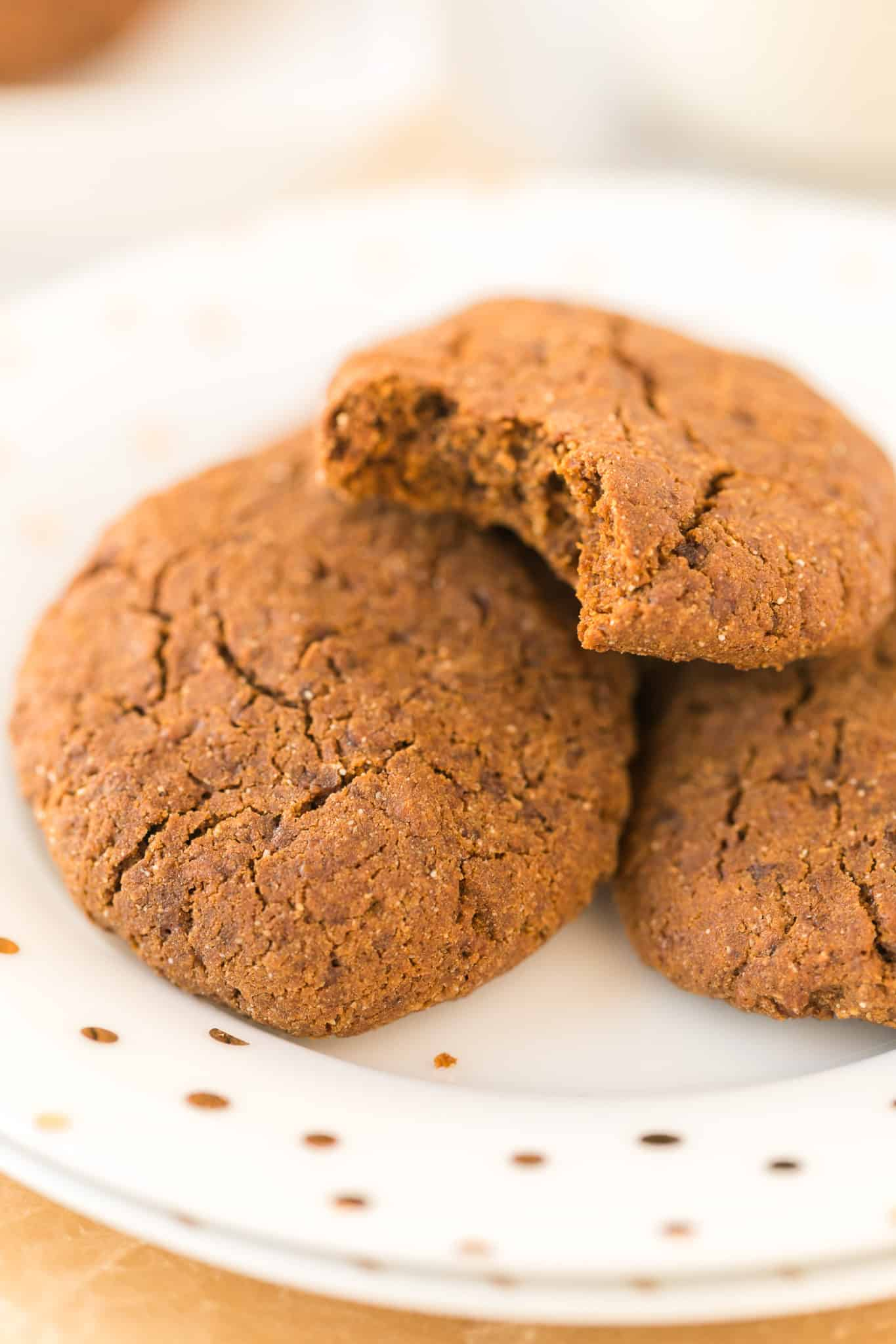 three molasses cookies on a plate with a bite taken out of one