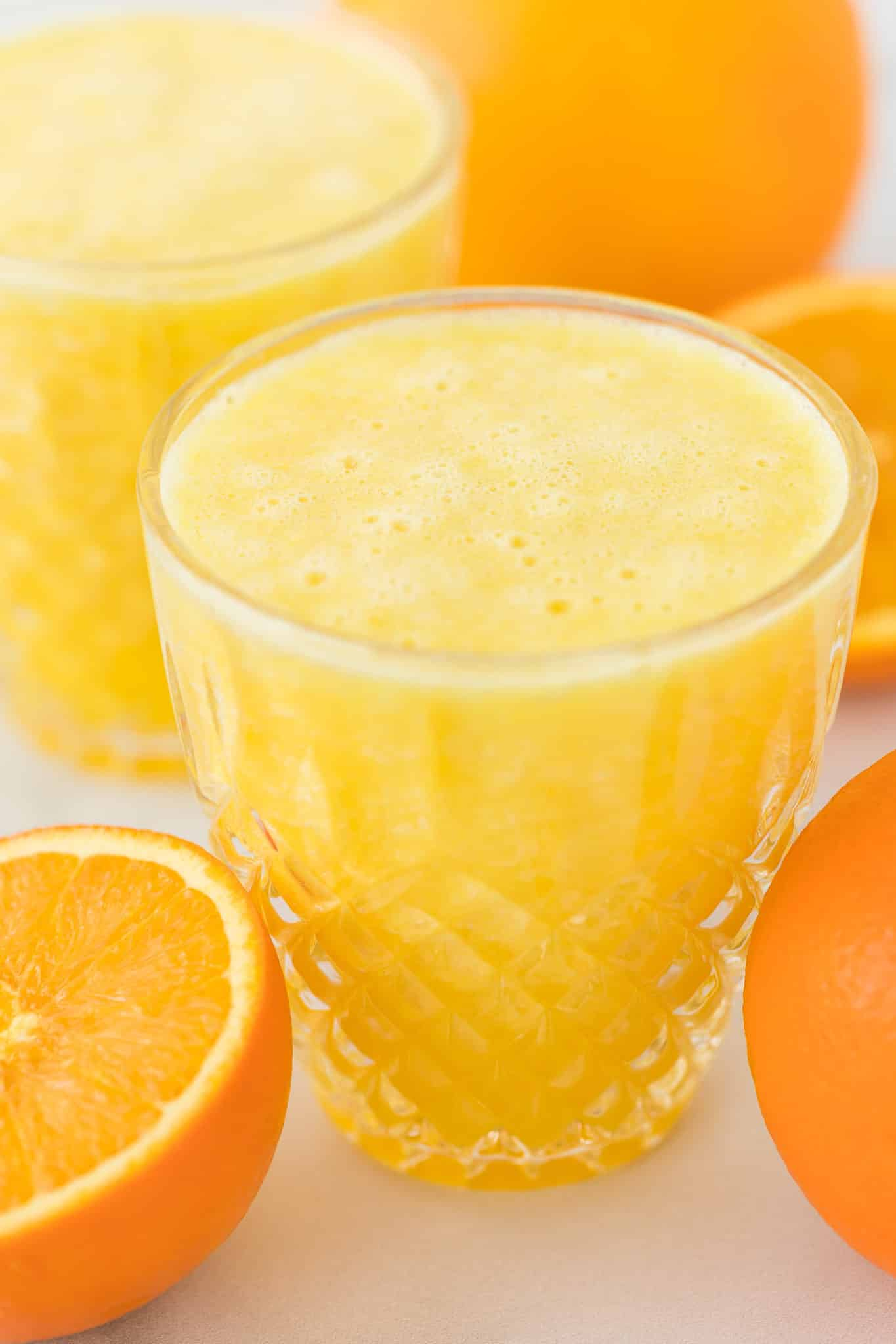 blended orange juice served in a pretty crystal glass surrounded by oranges
