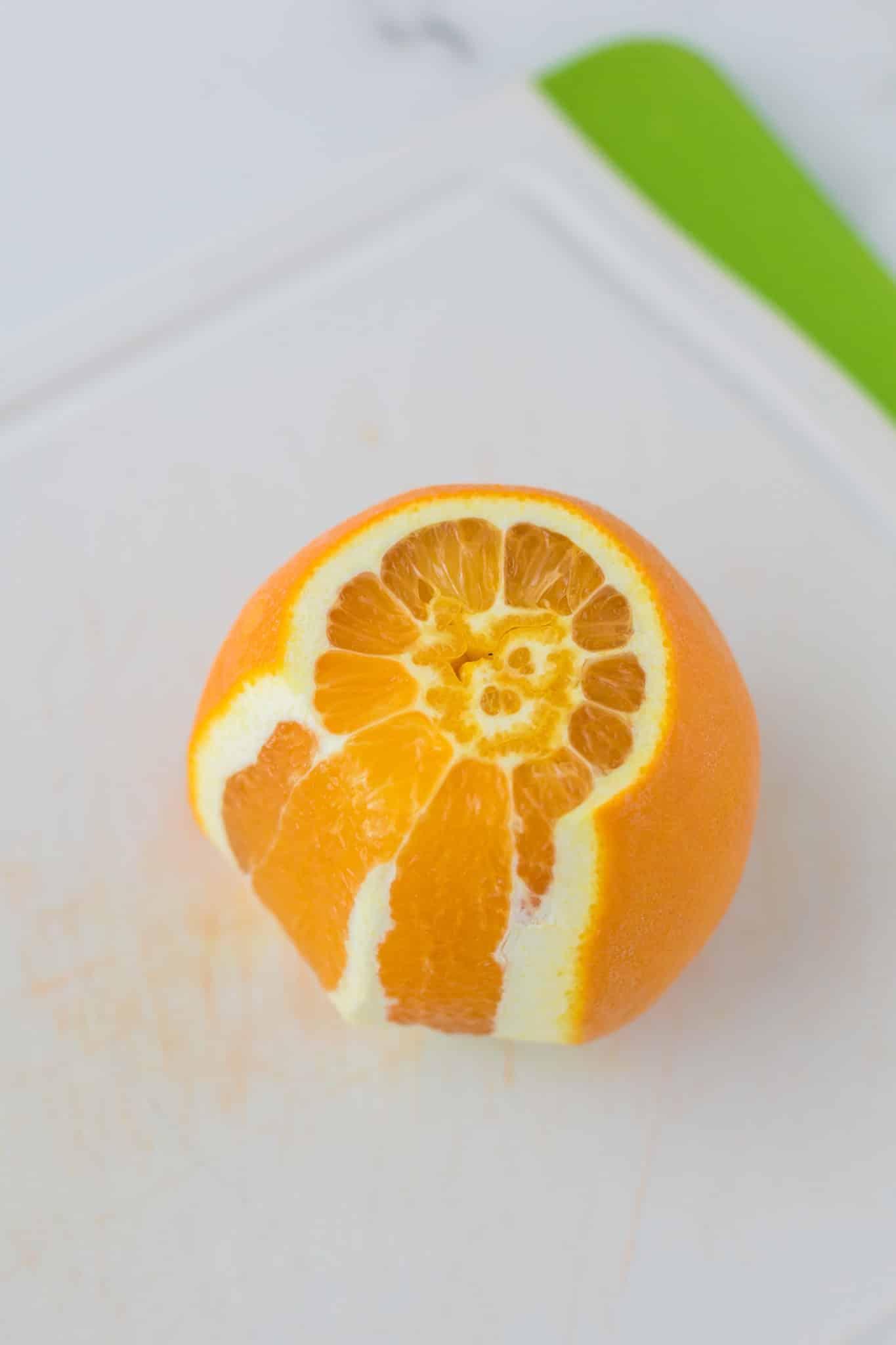 half-peeled orange on a cutting board