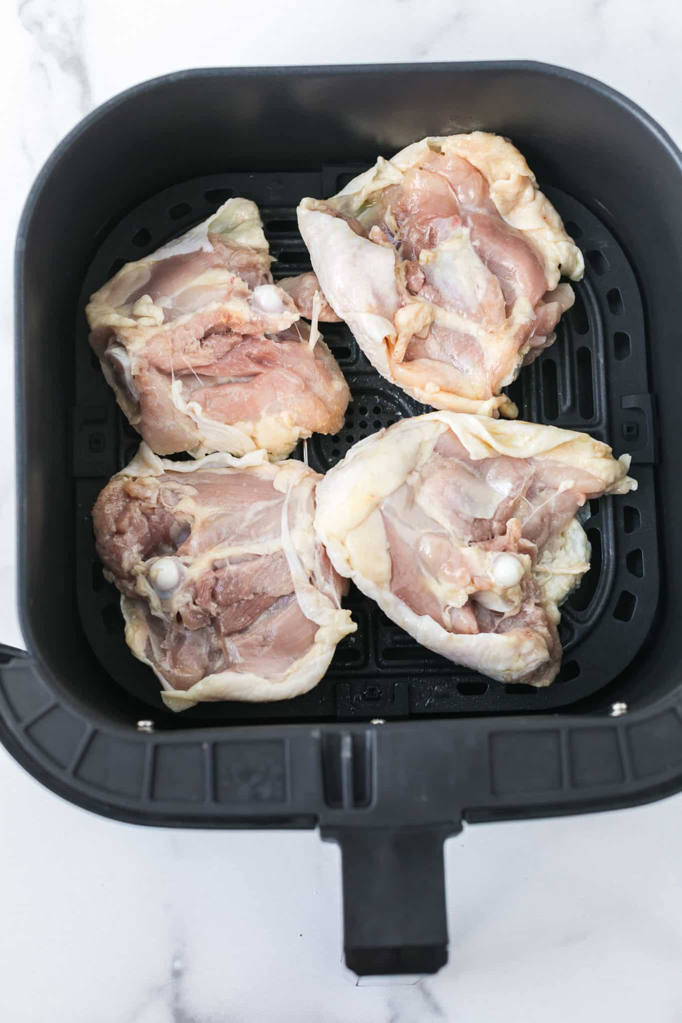 raw chicken thighs placed skin side down inside of an air fryer